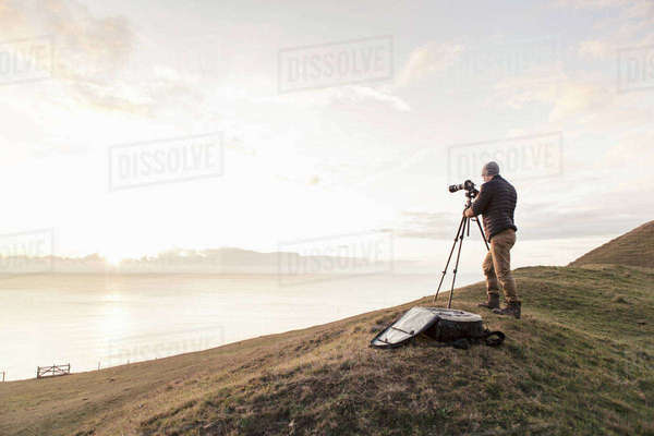 Rear view of hiker photographing sea through SLR camera while standing on hill Royalty-free stock photo