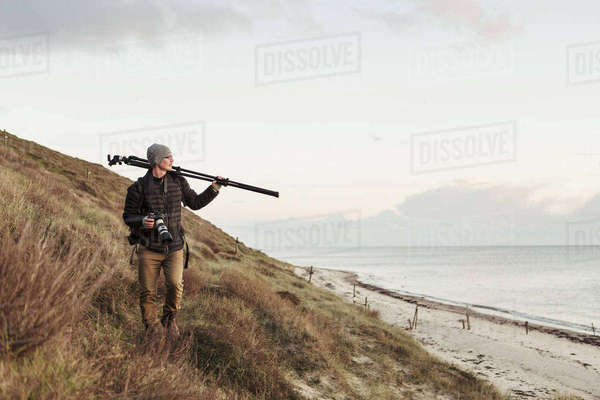 Photographer looking away while carrying tripod on hill by sea Royalty-free stock photo