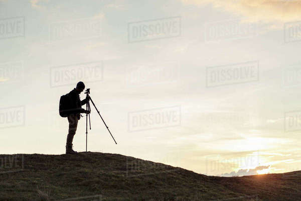 Side view of silhouette hiker fixing tripod on hill against sky during sunset Royalty-free stock photo