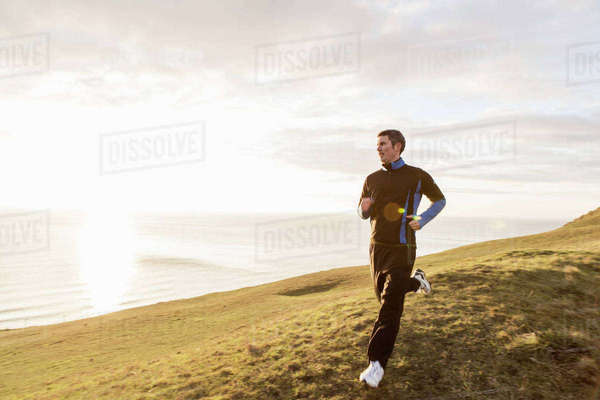 Full length of man jogging on hill by sea during sunny day Royalty-free stock photo