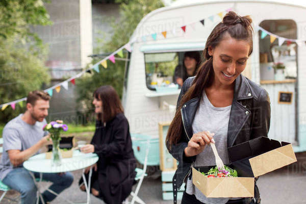 Female customer holding disposable salad box against food truck with friends and owner in background Royalty-free stock photo