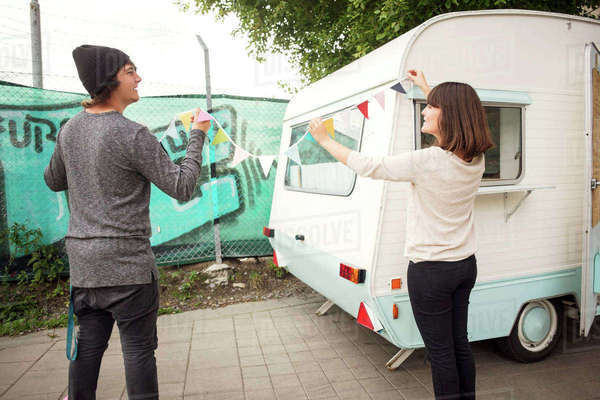 Rear view of male and female owners holding bunting by food truck on street Royalty-free stock photo