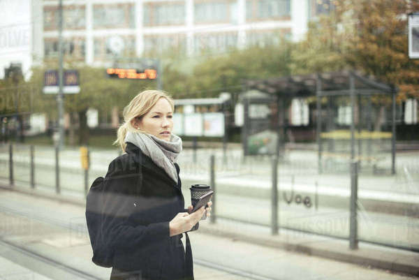 Mid adult businesswoman holding mobile phone and disposable coffee cup at tram station Royalty-free stock photo
