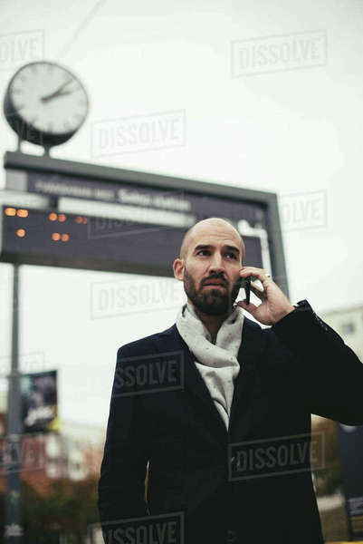 Low angle view of mid adult businessman talking on smart phone in city Royalty-free stock photo