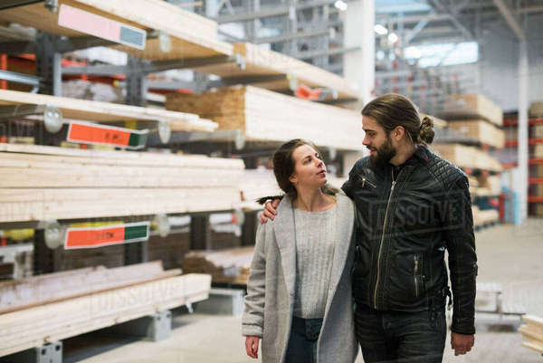Couple looking at each other while walking in hardware store warehouse Royalty-free stock photo
