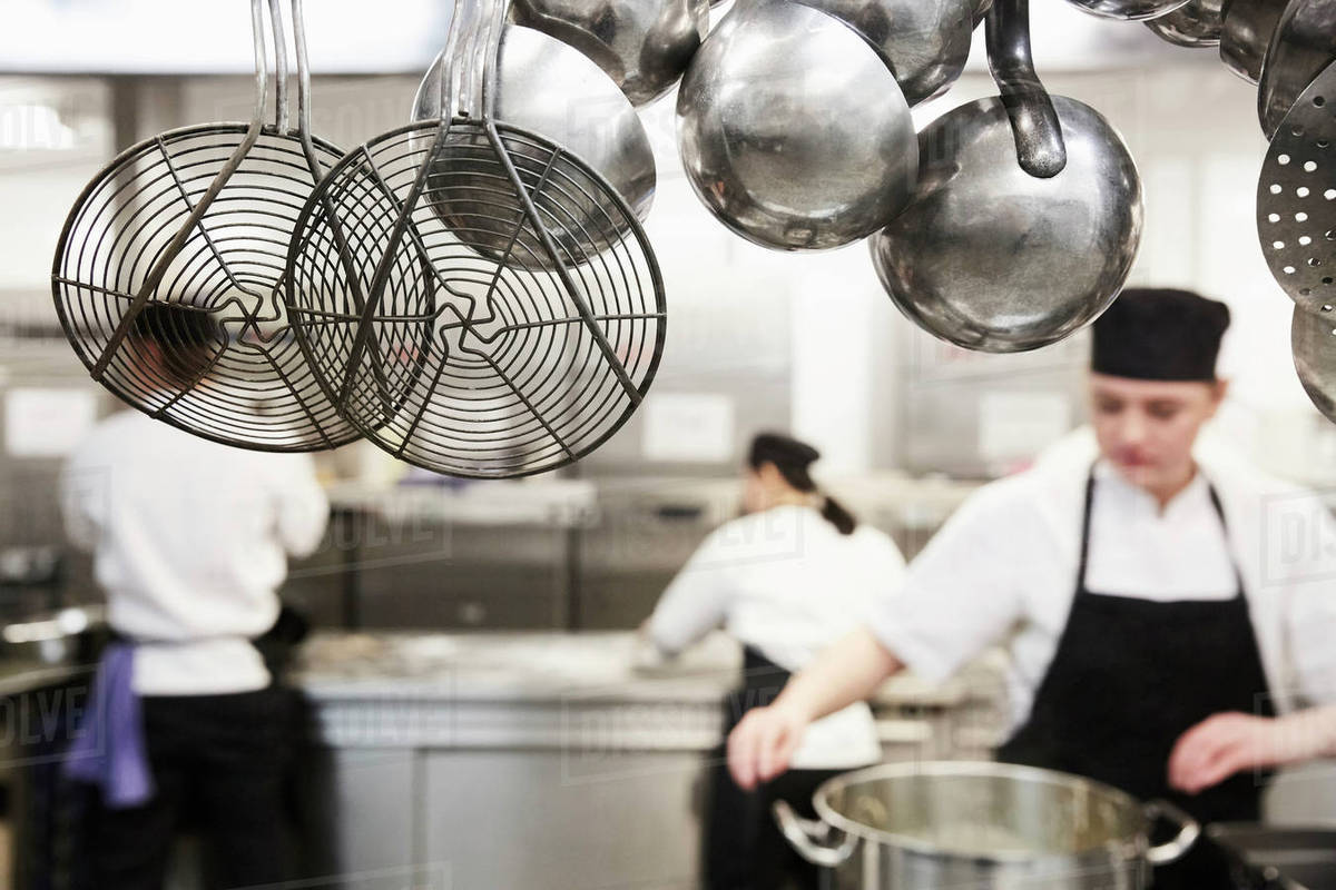 Kitchen utensils with chefs cooking in background at commercial kitchen  stock photo