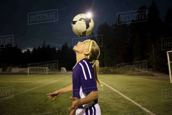 Side view of girl heading the ball on field against sky Royalty-free stock photo