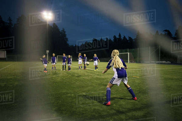 Girls playing soccer seen from goal post net on field against sky Royalty-free stock photo