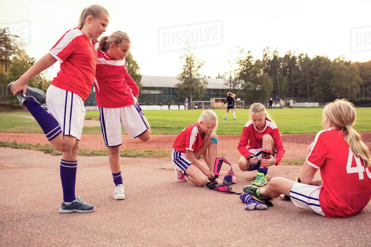 Girls stretching legs by friends wearing shin guards on field ... 66ce9d15cd4b