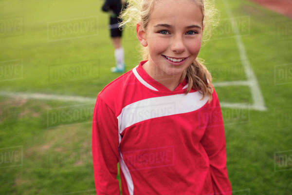 Portrait of happy girl standing on soccer field Royalty-free stock photo