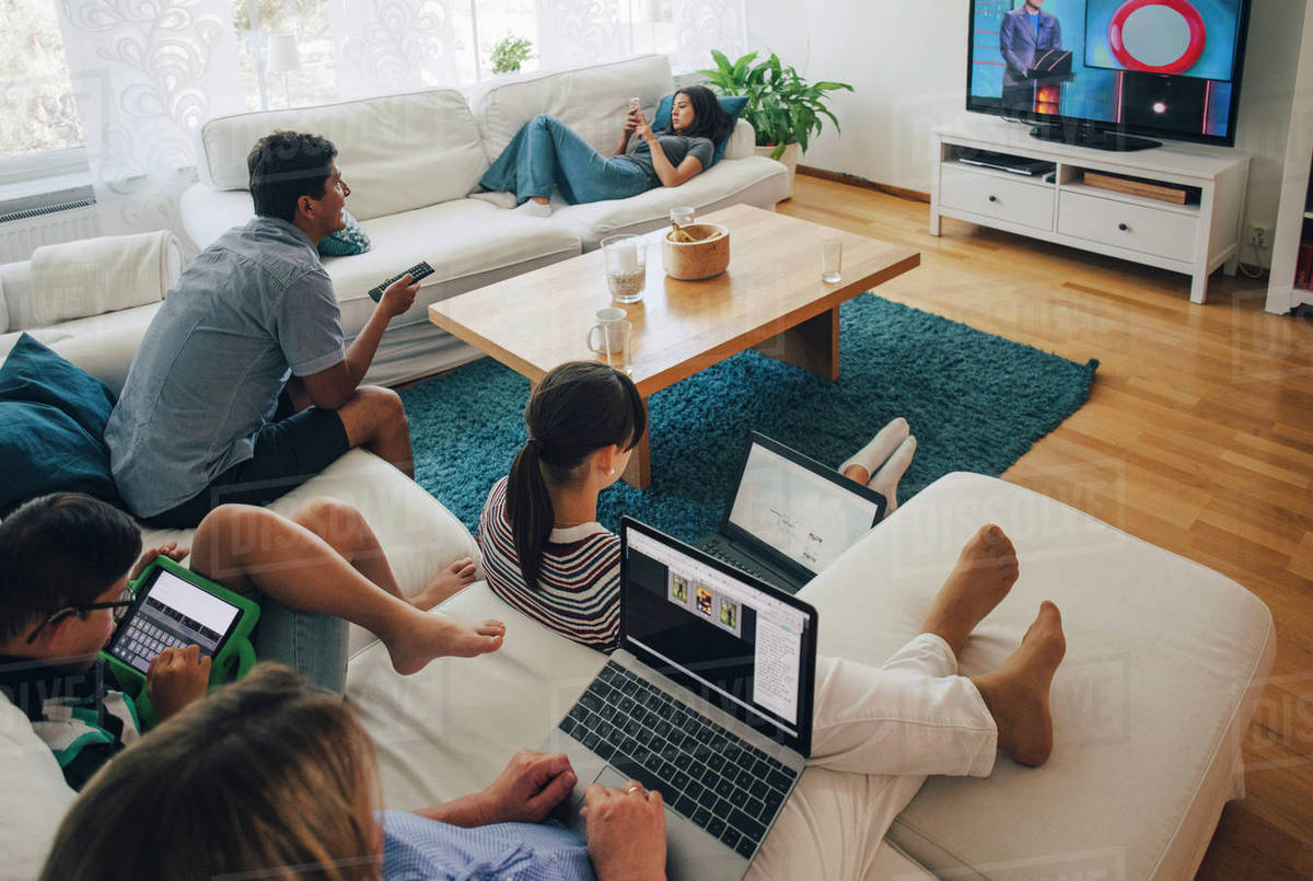 High angle view of family using technologies while relaxing in living room  at home stock photo