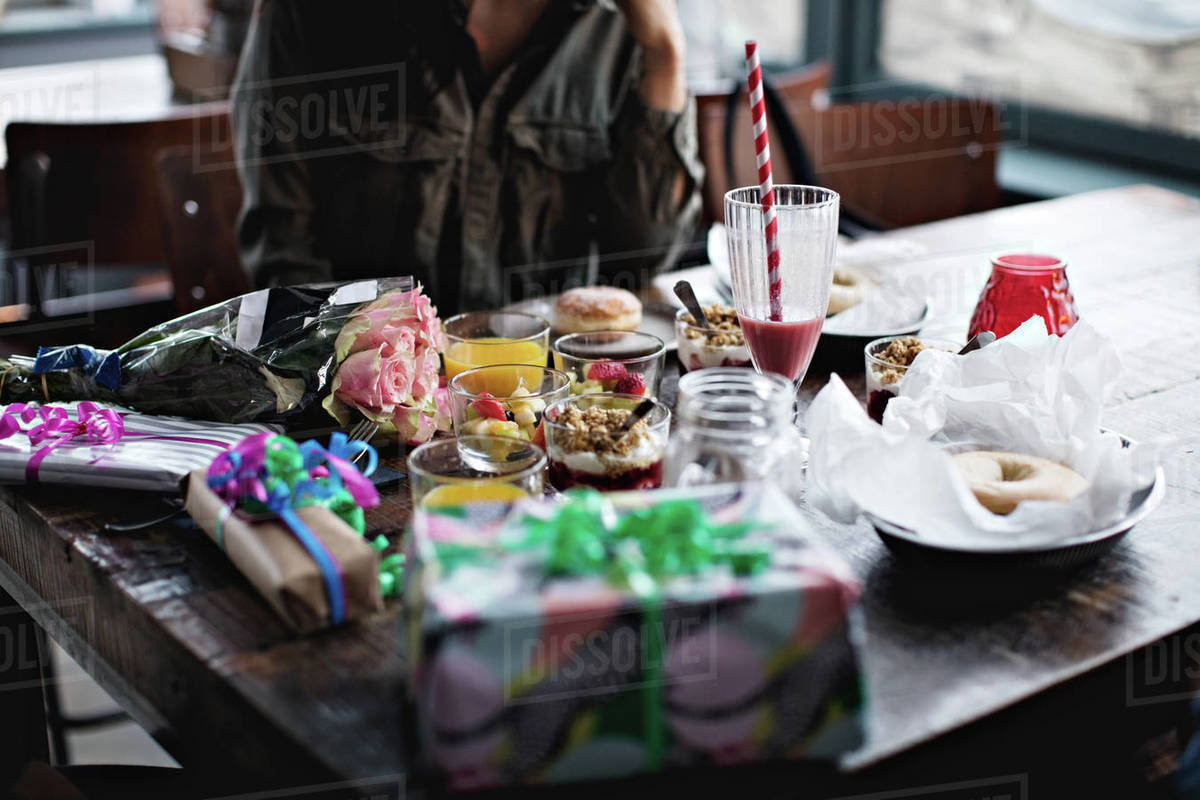 Midsection Of Young Woman Sitting With Birthday Presents And Food On Restaurant