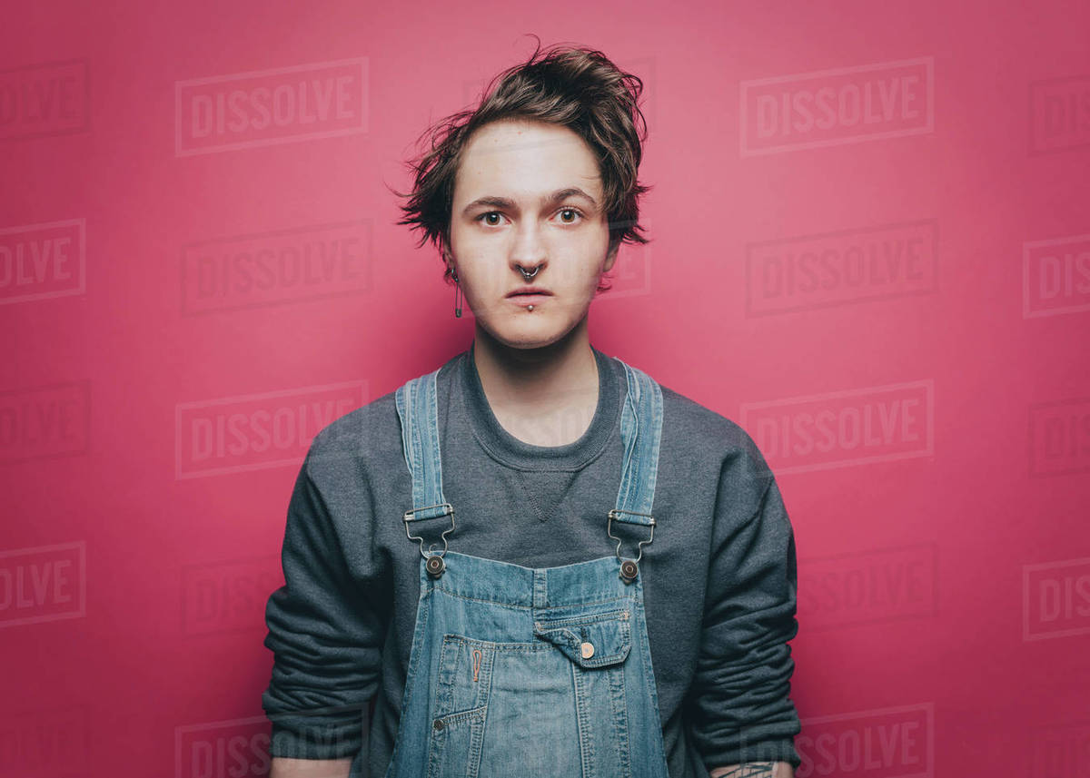 d64e12da Portrait of shocked young man wearing overalls against pink background