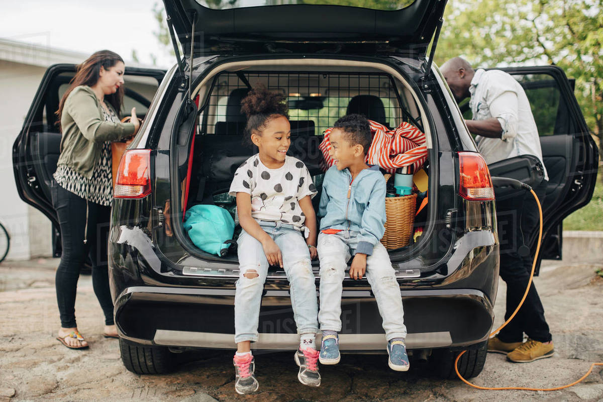 Full length of smiling siblings sitting on car trunk with parents standing in front yard Royalty-free stock photo
