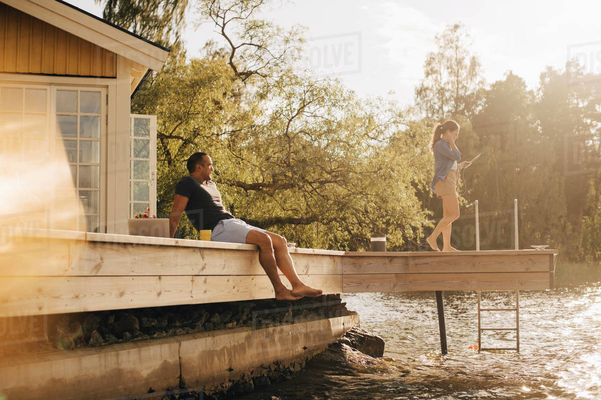 Mature man looking at woman using digital tablet while sitting on patio by lake Royalty-free stock photo