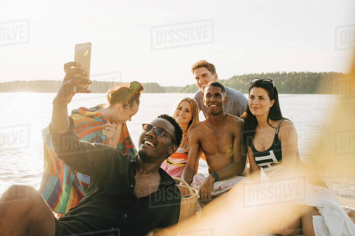 Man taking selfie with happy friends through smart phone on jetty in summer Royalty-free stock photo
