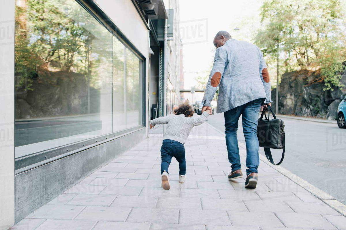 Rear view of father and daughter walking on sidewalk in city Royalty-free stock photo