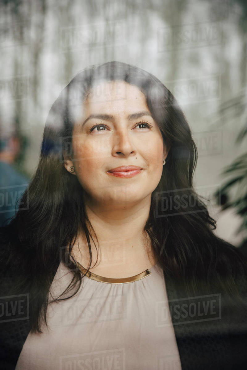 Thoughtful female entrepreneur looking through window while standing at office Royalty-free stock photo