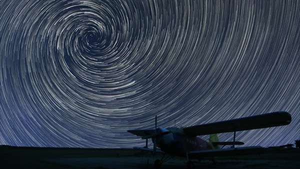 Star trails beautiful night sky, spiral star trails over small airport lonely airplane. Vortex star trails. Small airport, lonely airplane in dark sky Royalty-free stock video