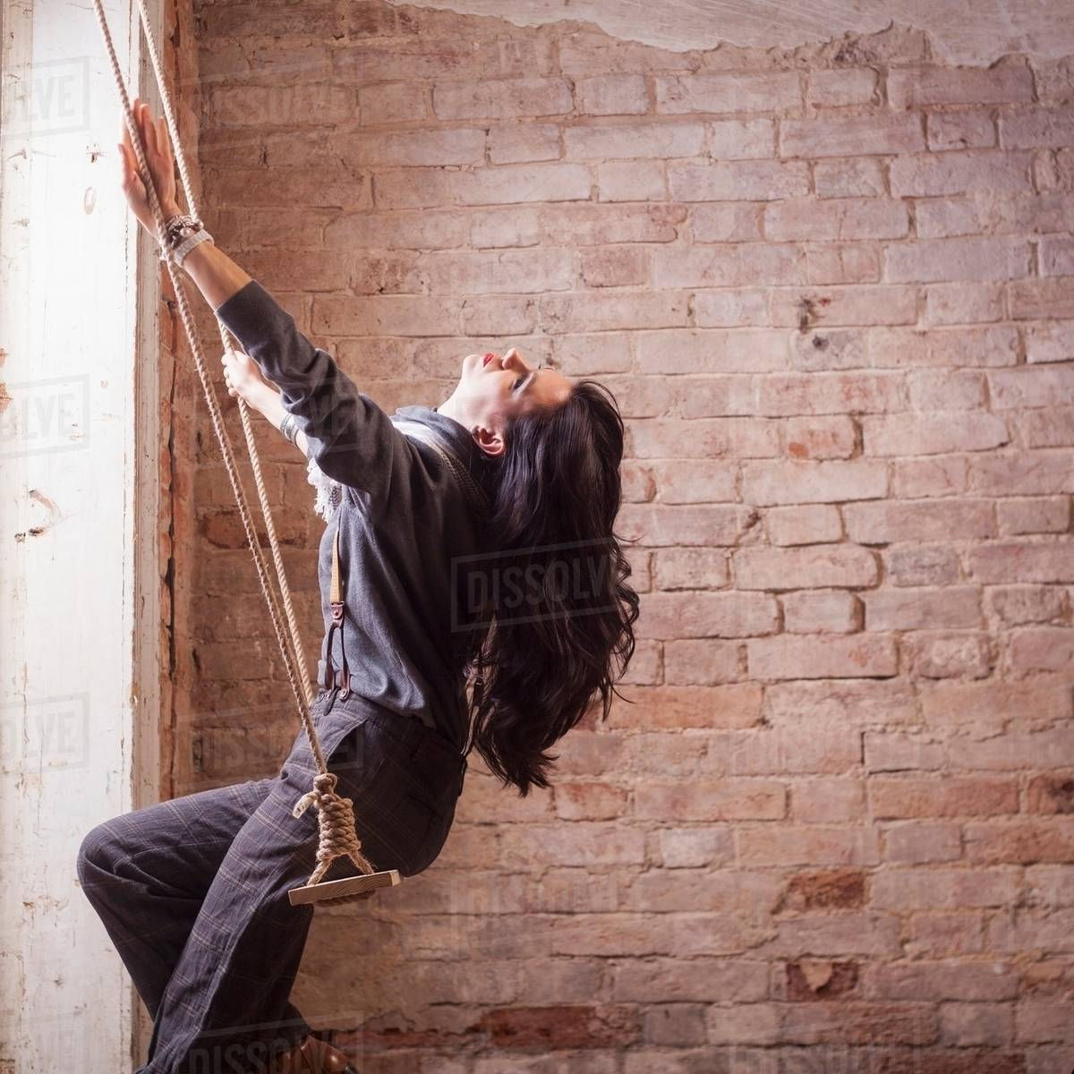 Side View Of Long Haired Mid Adult Woman Head Back Sitting On Swing In Front Brick Wall