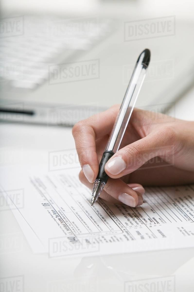 woman filling out a tax form - stock photo - dissolve