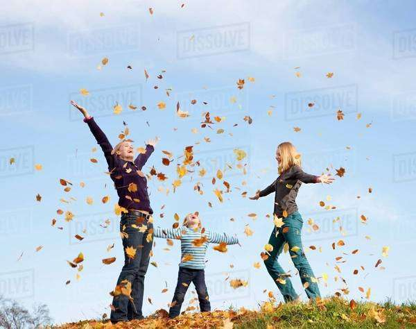 Woman, boy and girl throw autumn leaves Royalty-free stock photo
