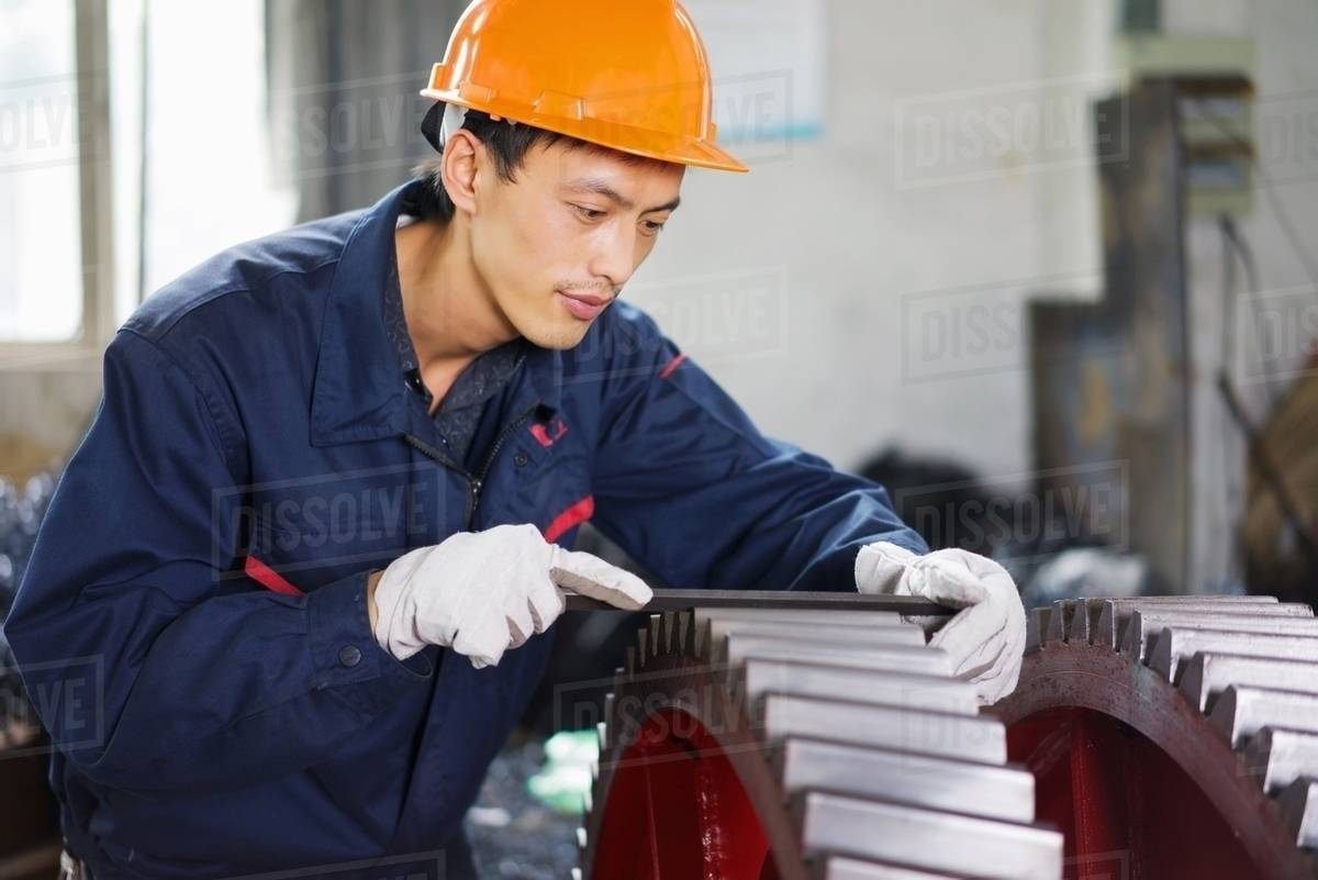Worker using equipment in crane manufacturing facility, China stock photo