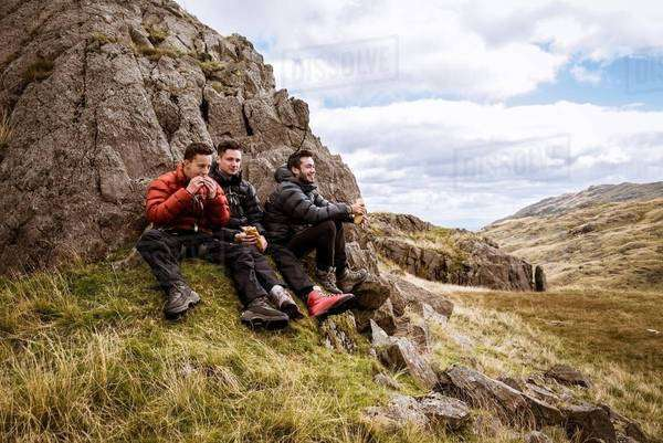 Three young male hiking friends eating sandwiches, The Lake District, Cumbria, UK Royalty-free stock photo