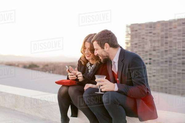 Two friends drinking together at party, woman showing man her mobile phone Royalty-free stock photo