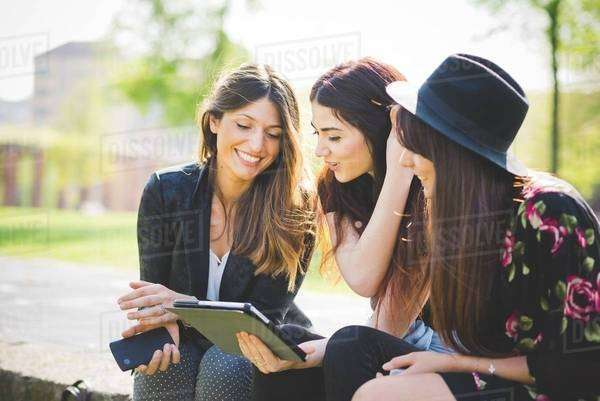 Three young female friends sharing update on digital tablet in park Royalty-free stock photo