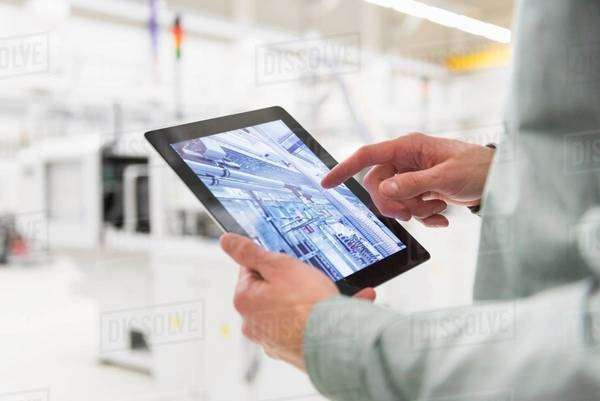 Male worker using digital tablet at tool manufacturing plant, focus on hands Royalty-free stock photo