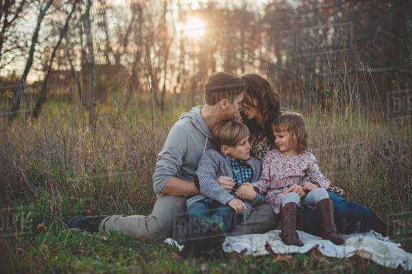 Young couple with son and daughter sitting on picnic blanket in field Royalty-free stock photo