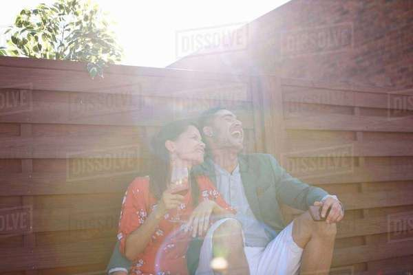 Relaxed mid adult couple laughing and drinking at rooftop party Royalty-free stock photo