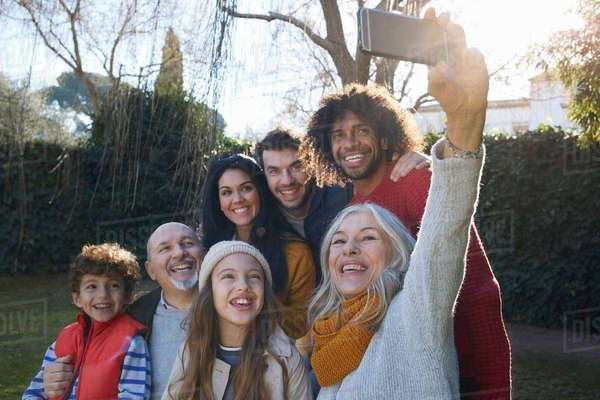 Multi generation family huddled together using smartphone to take selfie, smiling Royalty-free stock photo