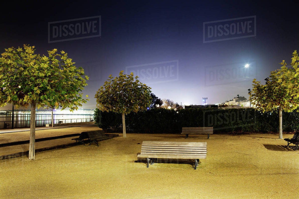 Empty Park Bench By River At Night Stock Photo Dissolve