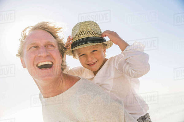 Father giving son piggyback smiling, wearing straw sun hat Royalty-free stock photo