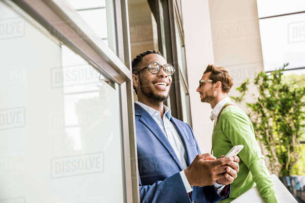 Businessman in office doorway using smartphone Royalty-free stock photo