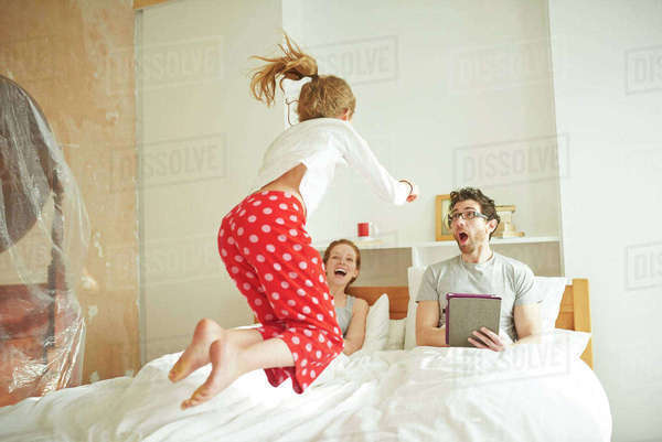 Mid adult couple having lie in whilst daughter jumps on bed Royalty-free stock photo