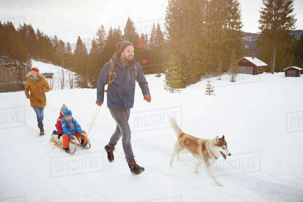 Parents with husky pulling sons on toboggan in snow covered landscape, Elmau, Bavaria, Germany Royalty-free stock photo