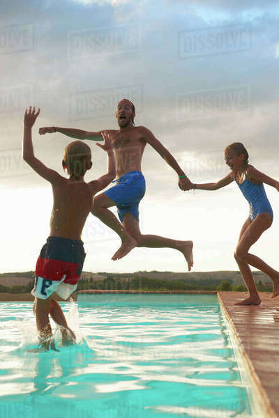 Man jumping into swimming pool with daughter and son, Buonconvento, Tuscany, Italy Royalty-free stock photo