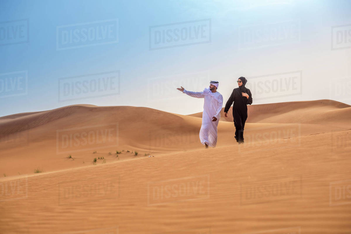 Couple wearing traditional middle eastern clothes pointing from desert  dune, Dubai, United Arab Emirates stock photo