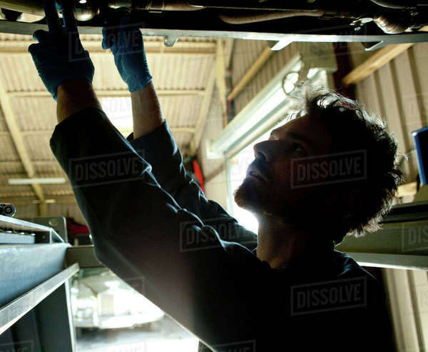 Male mechanic underneath car, looking for problem Royalty-free stock photo