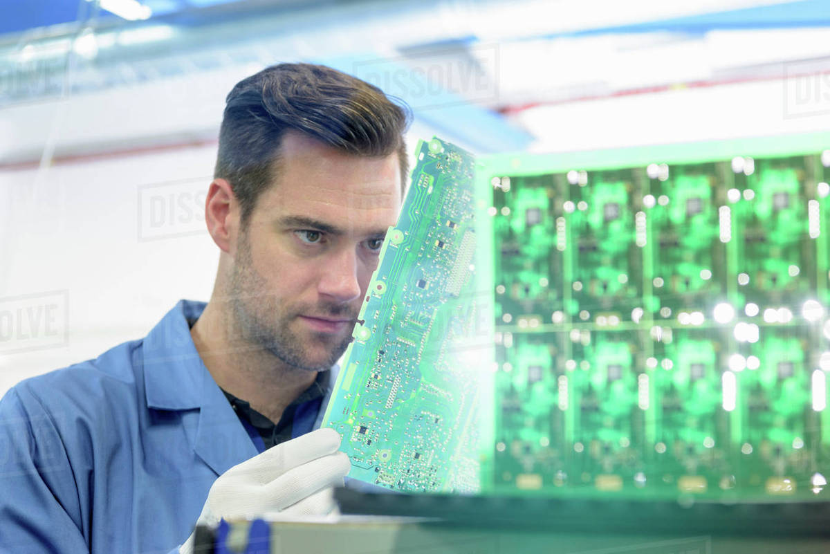 Worker Inspecting Circuit Boards In Board Assembly Factory