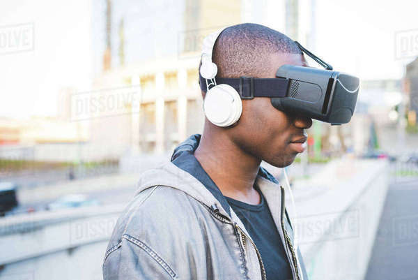 Young man outdoors, wearing virtual reality headset and headphones Royalty-free stock photo