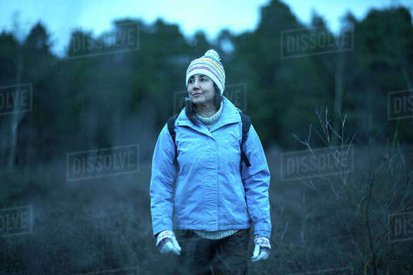 Female hiker hiking in forest at dusk Royalty-free stock photo