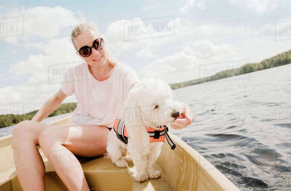 Woman petting coton de tulear dog in boat, Orivesi, Finland Royalty-free stock photo