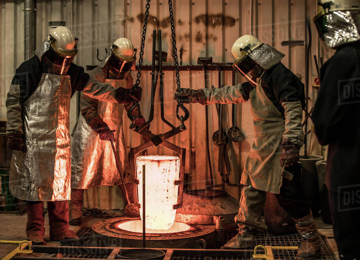 Male foundry workers winching white hot melting pot in bronze foundry stock  photo