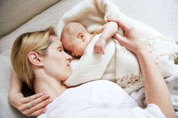 Sleeping mid adult woman with baby daughter wrapped in blanket Royalty-free stock photo