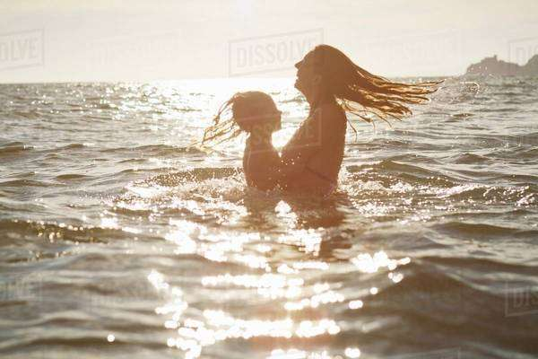 Mother and daughter playing in ocean Royalty-free stock photo