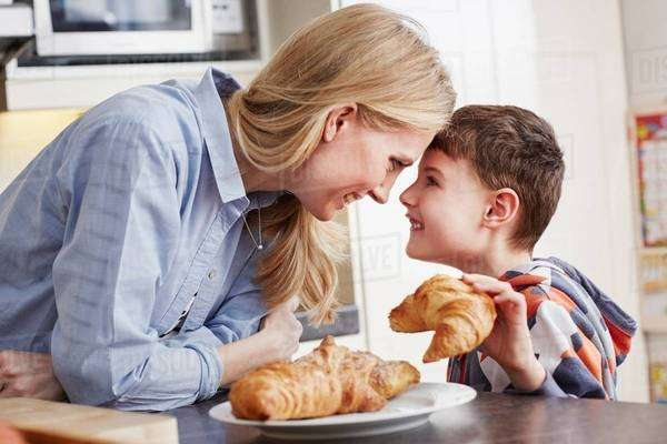 Boy holding croissant, face to face with mother Royalty-free stock photo